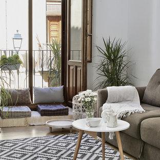 Modelo de salón cerrado, mediterráneo, de tamaño medio, con paredes blancas, suelo de madera clara, suelo beige y pared multimedia