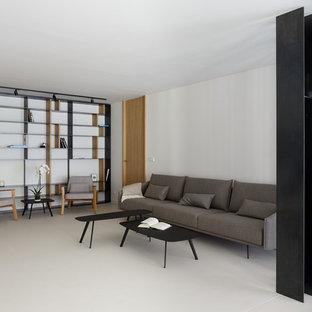 Foto de biblioteca en casa tipo loft, moderna, con paredes blancas, suelo de cemento, televisor colgado en la pared y suelo blanco