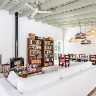 Diseño de salón abierto, bohemio, con paredes blancas, suelo de baldosas de terracota, estufa de leña, suelo naranja y televisor independiente