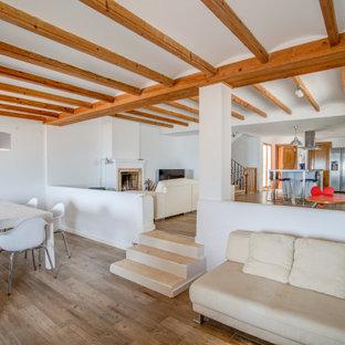 Imagen de salón abierto, actual, con paredes blancas, suelo de madera en tonos medios y suelo marrón