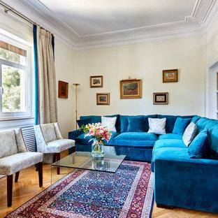Modelo de salón para visitas cerrado, actual, sin chimenea, con suelo de madera en tonos medios y paredes beige
