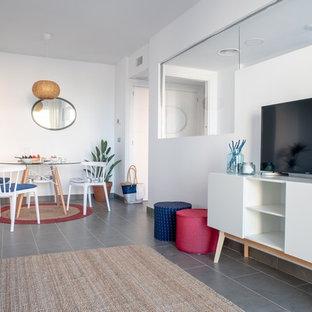 Foto de salón para visitas abierto, costero, con paredes blancas, televisor independiente y suelo gris