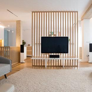 Modelo de salón para visitas cerrado, escandinavo, grande, con paredes blancas, suelo de madera clara, televisor colgado en la pared y suelo beige