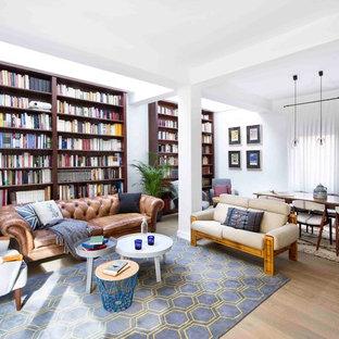 Imagen de biblioteca en casa abierta, vintage, de tamaño medio, sin chimenea y televisor, con paredes blancas y suelo de madera en tonos medios
