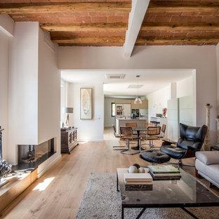 Imagen de salón abierto, actual, grande, sin televisor, con paredes blancas, suelo de madera en tonos medios, chimenea de esquina y marco de chimenea de yeso
