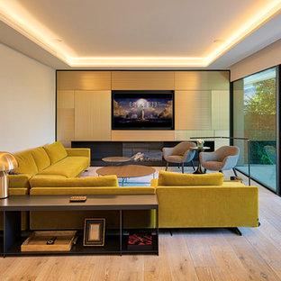 Imagen de salón para visitas cerrado, actual, con paredes blancas, suelo de madera clara, chimenea lineal, marco de chimenea de yeso, pared multimedia y suelo beige