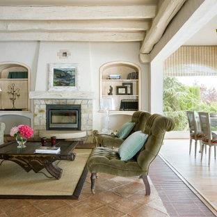 Ejemplo de salón para visitas abierto, mediterráneo, grande, con paredes blancas, chimenea tradicional, marco de chimenea de piedra y suelo beige