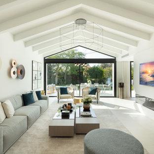 他の地域の巨大な地中海スタイルのおしゃれなLDK (白い壁、横長型暖炉、壁掛け型テレビ、ベージュの床) の写真
