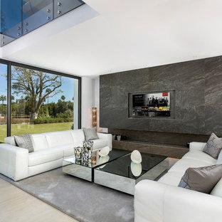 Modelo de salón abierto, actual, grande, con paredes blancas, pared multimedia y suelo beige