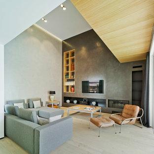 Diseño de salón abierto, minimalista, grande, con paredes grises, suelo de madera clara, televisor colgado en la pared, chimenea lineal y suelo beige