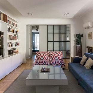 Modelo de salón abierto, minimalista, de tamaño medio, con paredes blancas, suelo de madera clara, televisor independiente y suelo beige