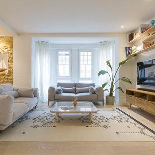 Modelo de salón escandinavo con paredes blancas, suelo de madera clara, televisor colgado en la pared y suelo beige
