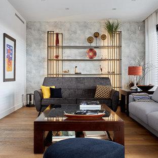 Modelo de salón para visitas cerrado, actual, con paredes blancas, suelo de madera en tonos medios, chimenea lineal, marco de chimenea de metal, televisor colgado en la pared y suelo marrón