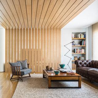 Modelo de salón cerrado, contemporáneo, grande, sin chimenea y televisor, con paredes blancas, suelo de madera en tonos medios y suelo marrón