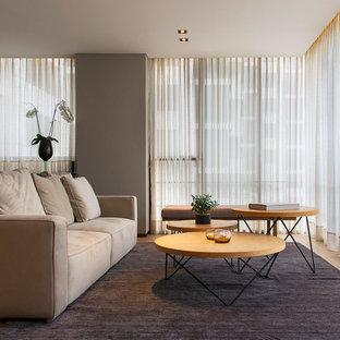 Diseño de salón contemporáneo con paredes grises, suelo de madera en tonos medios y suelo marrón