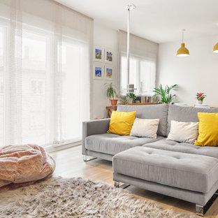 Ejemplo de salón abierto, nórdico, grande, con paredes blancas, suelo de madera en tonos medios y pared multimedia