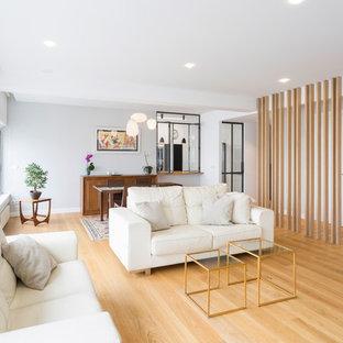 Ejemplo de salón para visitas abierto, actual, con paredes blancas, suelo de madera clara y suelo beige