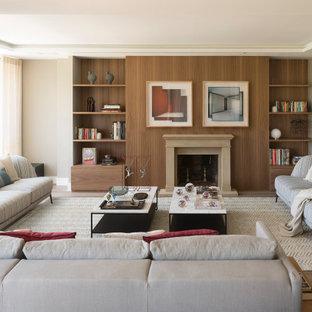 Diseño de biblioteca en casa actual, grande, sin televisor, con paredes beige, chimenea tradicional y suelo de madera en tonos medios