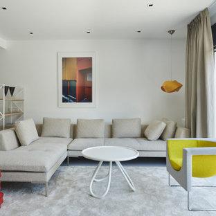Ejemplo de salón abierto, actual, de tamaño medio, con paredes blancas, suelo de cemento, televisor colgado en la pared y suelo gris
