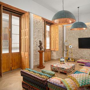 Imagen de salón bohemio con paredes beige, suelo de madera clara, televisor colgado en la pared y suelo beige