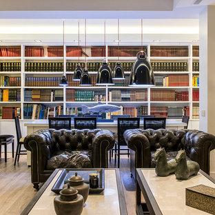 Imagen de biblioteca en casa abierta, contemporánea, grande, sin chimenea, con paredes blancas y suelo de madera en tonos medios
