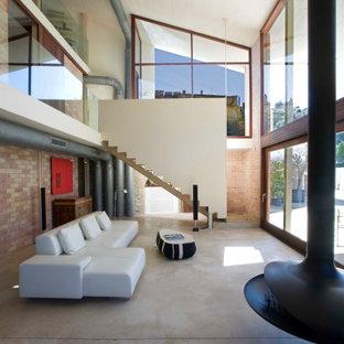 Idée de décoration pour un grand salon design ouvert avec un mur rouge, un sol en carrelage de porcelaine, cheminée suspendue, un manteau de cheminée en métal, aucun téléviseur, un sol gris et un mur en parement de brique.