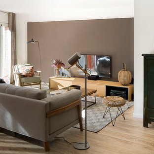 Photo of a medium sized enclosed living room in Barcelona with brown walls, medium hardwood flooring, no fireplace, a wall mounted tv and brown floors.