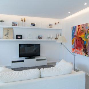 Foto de salón contemporáneo con paredes blancas, suelo de cemento, televisor independiente y suelo gris