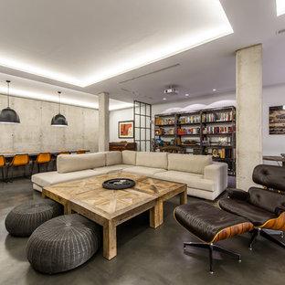 Ejemplo de biblioteca en casa abierta, urbana, extra grande, con paredes grises y suelo de cemento
