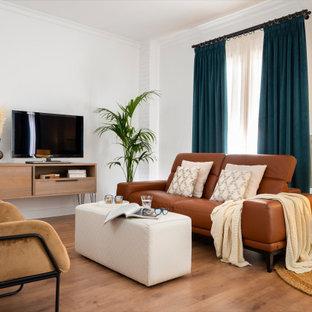 Modelo de salón abierto, actual, con paredes blancas, suelo de madera en tonos medios, televisor independiente y suelo marrón
