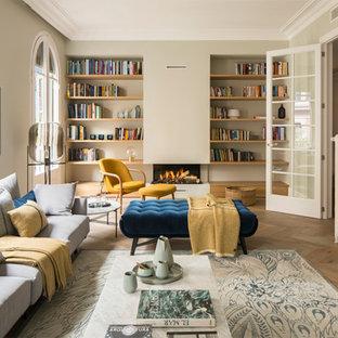 Ejemplo de biblioteca en casa cerrada, mediterránea, grande, sin televisor, con paredes beige, suelo de madera en tonos medios, estufa de leña, marco de chimenea de yeso y suelo beige