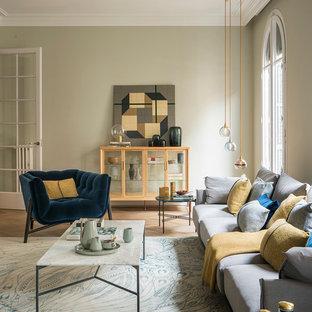 Modelo de salón para visitas cerrado, mediterráneo, grande, sin televisor, con paredes beige, suelo de madera en tonos medios, marco de chimenea de yeso y suelo beige