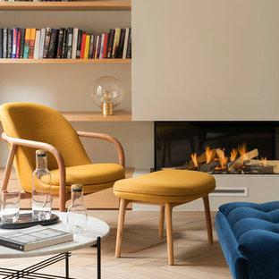 バルセロナの広い地中海スタイルのおしゃれな独立型リビング (ライブラリー、ベージュの壁、無垢フローリング、薪ストーブ、漆喰の暖炉まわり、テレビなし、ベージュの床) の写真