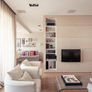 Foto de salón para visitas abierto, contemporáneo, grande, sin chimenea, con paredes blancas, suelo de madera en tonos medios y televisor colgado en la pared