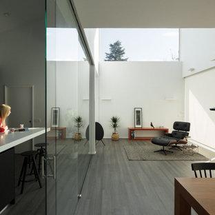 Diseño de salón abierto, minimalista, con paredes blancas, suelo de madera oscura y suelo gris