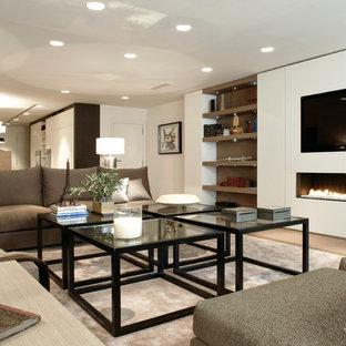 Modelo de salón para visitas abierto, contemporáneo, de tamaño medio, con paredes blancas, suelo de madera clara, chimenea lineal y televisor colgado en la pared