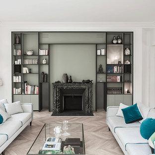 Esempio di un ampio soggiorno design aperto con sala formale, pareti verdi, parquet chiaro, cornice del camino in pietra e nessuna TV
