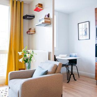 Exemple d'un salon avec une bibliothèque ou un coin lecture tendance de taille moyenne et ouvert avec un mur blanc, un sol en bois clair, aucune cheminée et aucun téléviseur.