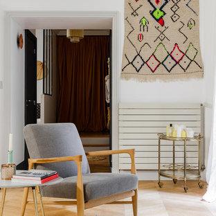 Idée de décoration pour un salon design de taille moyenne et fermé avec un mur blanc, un sol en bois clair, aucune cheminée et aucun téléviseur.