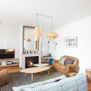 Cette photo montre un salon tendance de taille moyenne et ouvert avec un manteau de cheminée en béton, un mur blanc, un sol en bois brun, une cheminée standard et un sol marron.