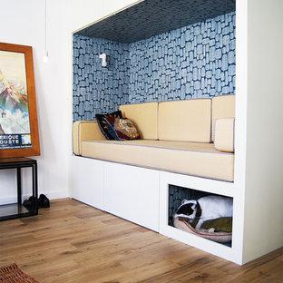 Réalisation d'un petit salon avec une bibliothèque ou un coin lecture nordique ouvert avec un mur blanc, un sol en bois brun, aucune cheminée et aucun téléviseur.