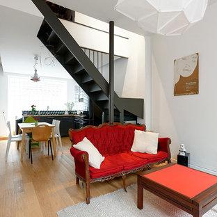Idée de décoration pour un salon design de taille moyenne et ouvert avec un mur blanc, un sol en bois clair, aucune cheminée et aucun téléviseur.