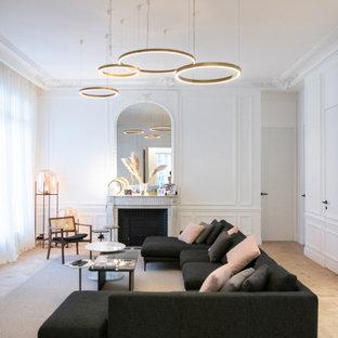 Exemple d'un grand salon tendance fermé avec un mur blanc, un sol en bois clair, une cheminée standard, un manteau de cheminée en pierre, aucun téléviseur, un sol beige, une salle de réception et boiseries.