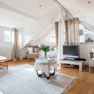 Island style loft-style medium tone wood floor and brown floor living room photo in Paris with white walls and a tv stand