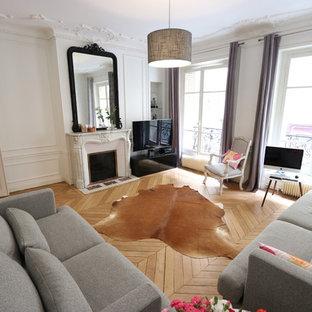Inspiration pour un salon minimaliste de taille moyenne et ouvert avec un mur blanc, un sol en bois brun, une cheminée standard, un téléviseur indépendant et un sol beige.