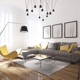Imagen de salón abierto, moderno, pequeño, sin chimenea, con paredes blancas, suelo de madera en tonos medios y televisor colgado en la pared