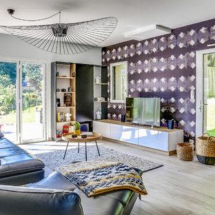 Inspiration pour un salon bohème avec un mur multicolore, un sol en bois clair, un téléviseur indépendant et un sol beige.