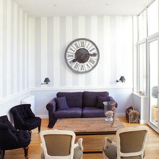 Aménagement d'un salon classique de taille moyenne et fermé avec un sol en bois brun, aucun téléviseur et un mur violet.