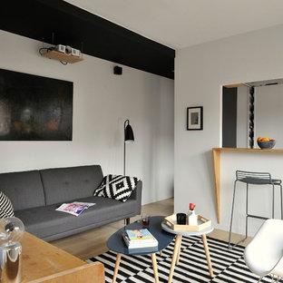 Idée de décoration pour un salon nordique de taille moyenne et fermé avec un bar de salon, un mur blanc, un sol en bois clair, aucune cheminée et aucun téléviseur.