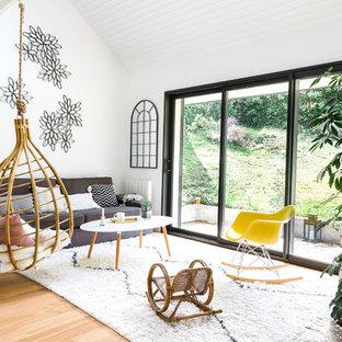 Réalisation d'un salon nordique ouvert avec une salle de réception, un mur blanc, un sol en bois clair et un sol beige.